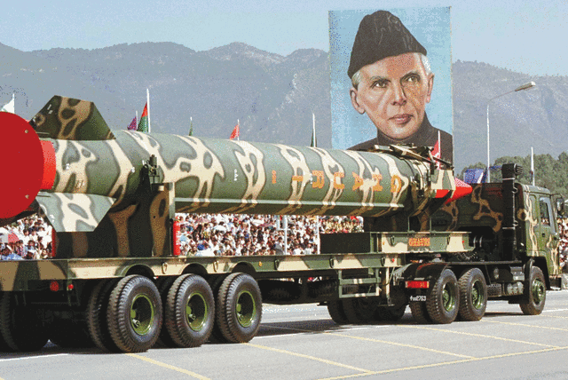 A PAKISTAN ARMY vehicle carrying the long-range surface-to-surface Ghauri missile passes a portrait of the nation's founder, Muhammad Ali Jinnah, in 1999. (photo credit: REUTERS)